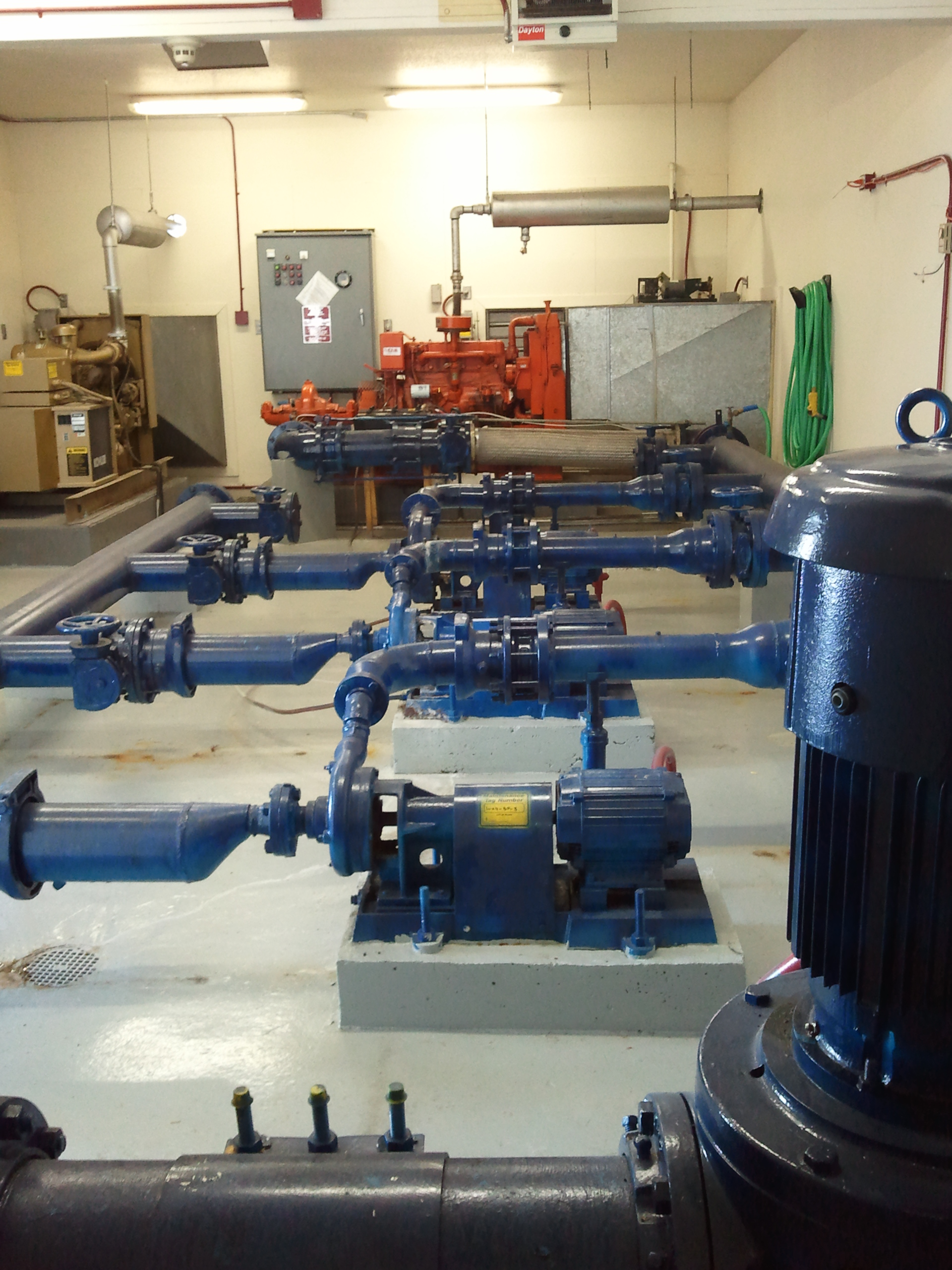 photo of a water pump and pressure pumps connected by blue pipes